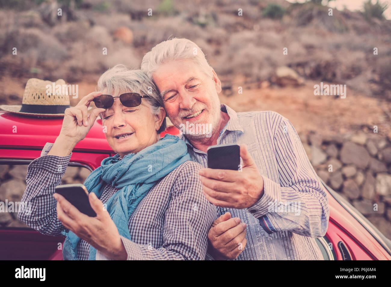 Bellissima l uomo e la donna giovane senior coppia utilizza lo smartphone all'aperto in attività di svago di controllo internet per i messaggi di posta elettronica e i contatti degli amici di vacanza. Immagini Stock