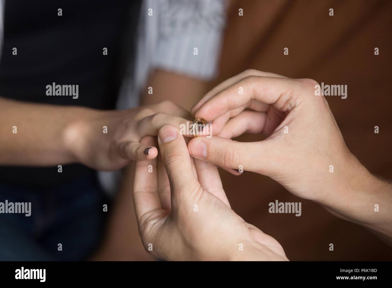 Close up uomo mettere l'anello nuziale sul dito di donna Immagini Stock