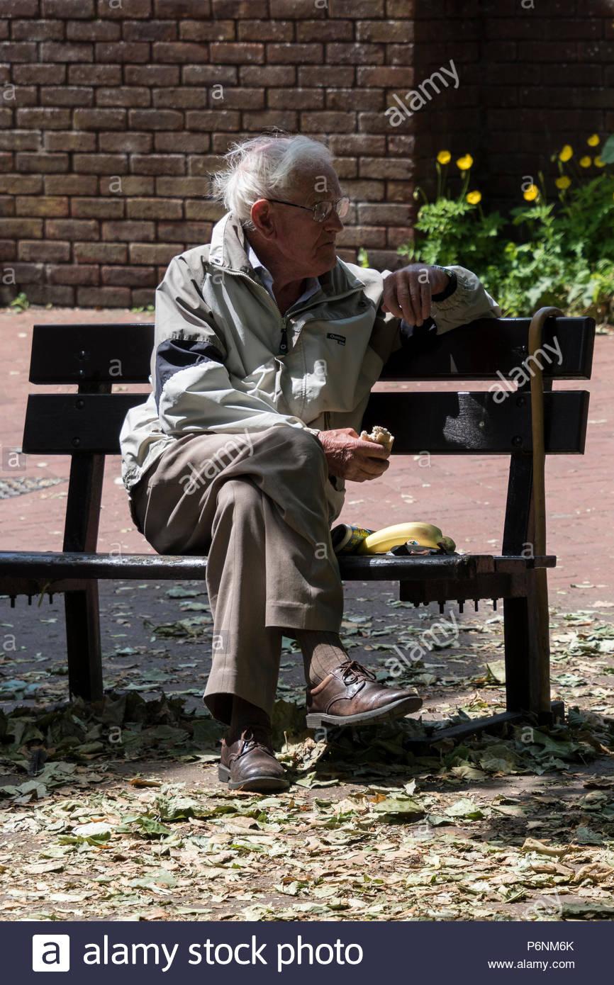 OAP mangiare il pranzo in un centro storico banco, Ringwood, Hampshire, Inghilterra, Regno Unito Immagini Stock
