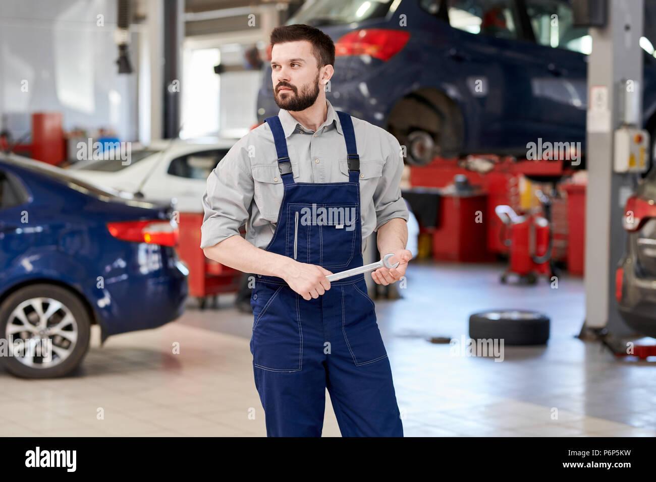 Barbuto meccanico che lavora in auto di servizio Immagini Stock