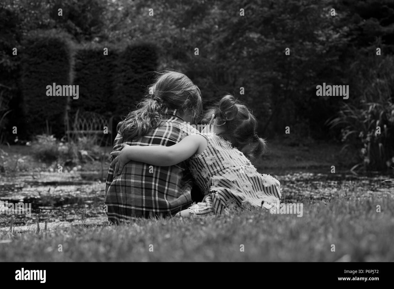 Bambina che abbraccia il suo amico da un laghetto. Immagini Stock