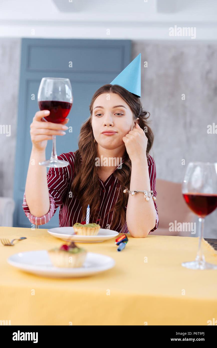 Giovane donna proponendo un toast frequentando festa di compleanno Immagini Stock