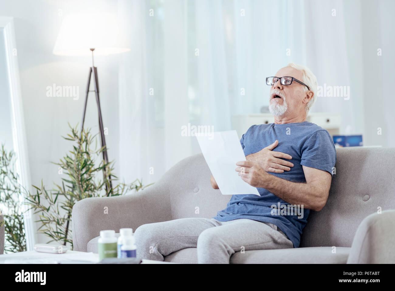 Stupito senior Man aventi i bruciori di stomaco Foto Stock