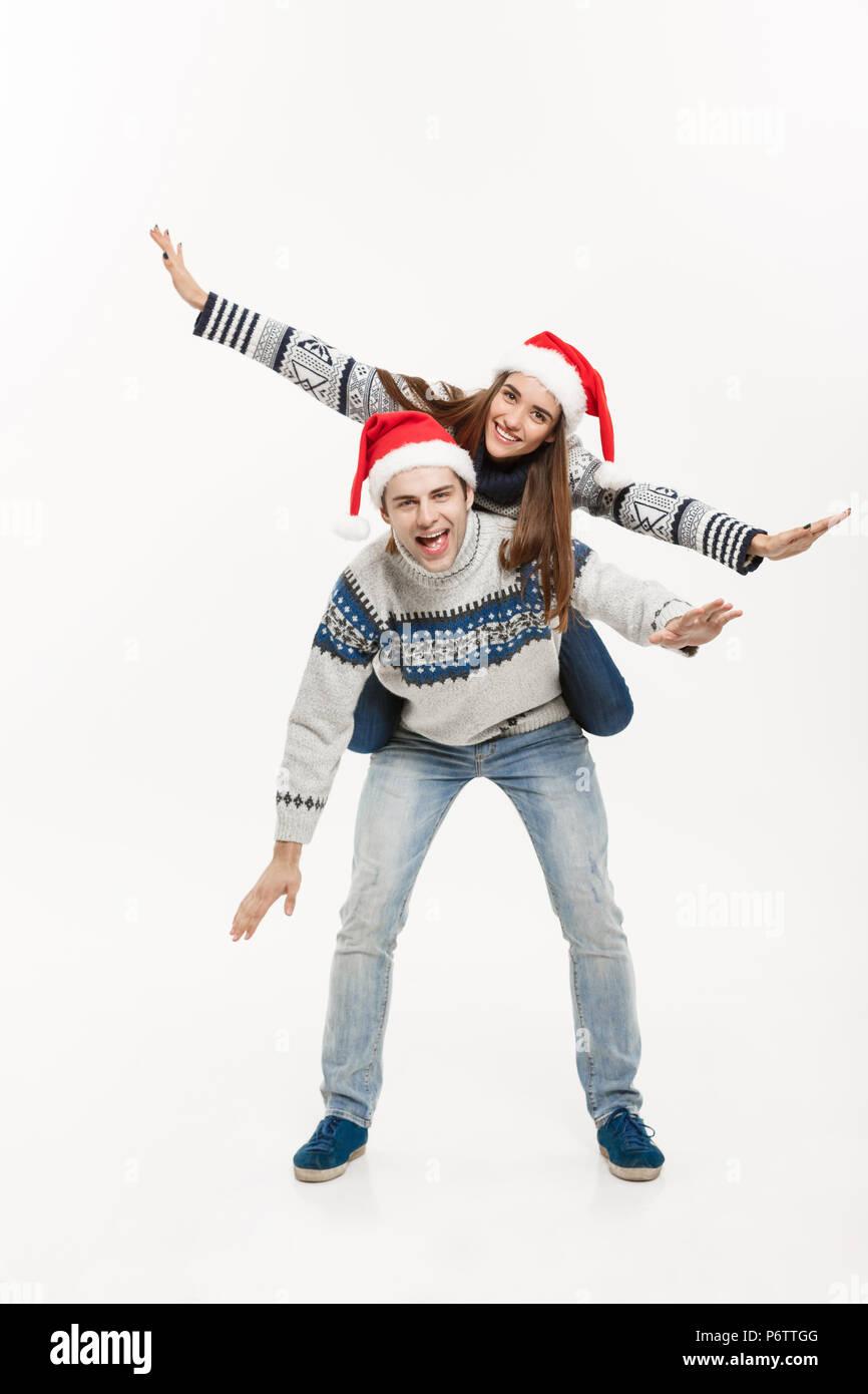 Concetto di natale - full-length giovane coppia felice in maglioni godendo piggyback ride isolato bianco su sfondo grigio Immagini Stock