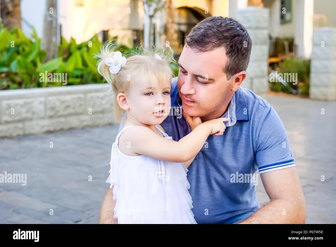 Ritratto di piccolo grazioso toddler blondy ragazza in abito bianco abbracciando il suo padre e raccontando qualcosa durante la passeggiata nel parco della città. Famiglia attiva le Immagini Stock