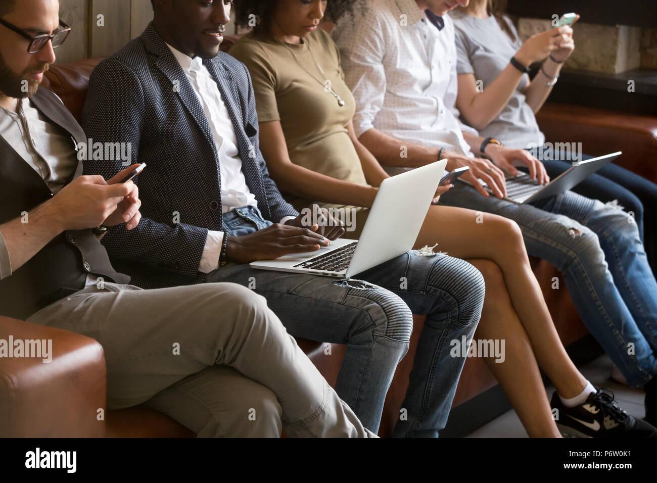 Close up di tecnologia ossessionato multirazziale gente seduta in qu Immagini Stock