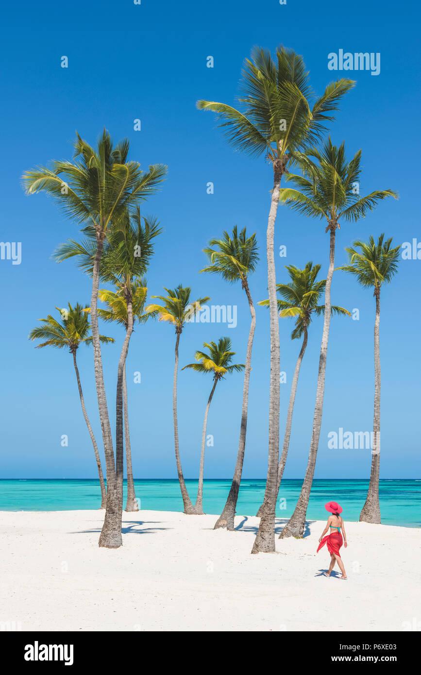 Spiaggia Juanillo (playa Juanillo), Punta Cana, Repubblica Dominicana. Donna che cammina su una spiaggia orlata di palme (MR). Immagini Stock
