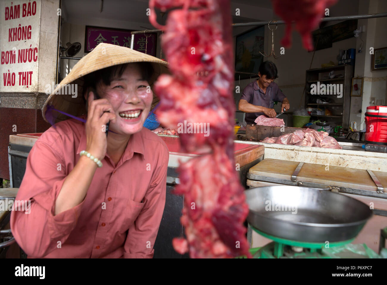 Donna macellerie vendono carne e sul telefono con cappello conico a Can Tho, Vietnam Foto Stock
