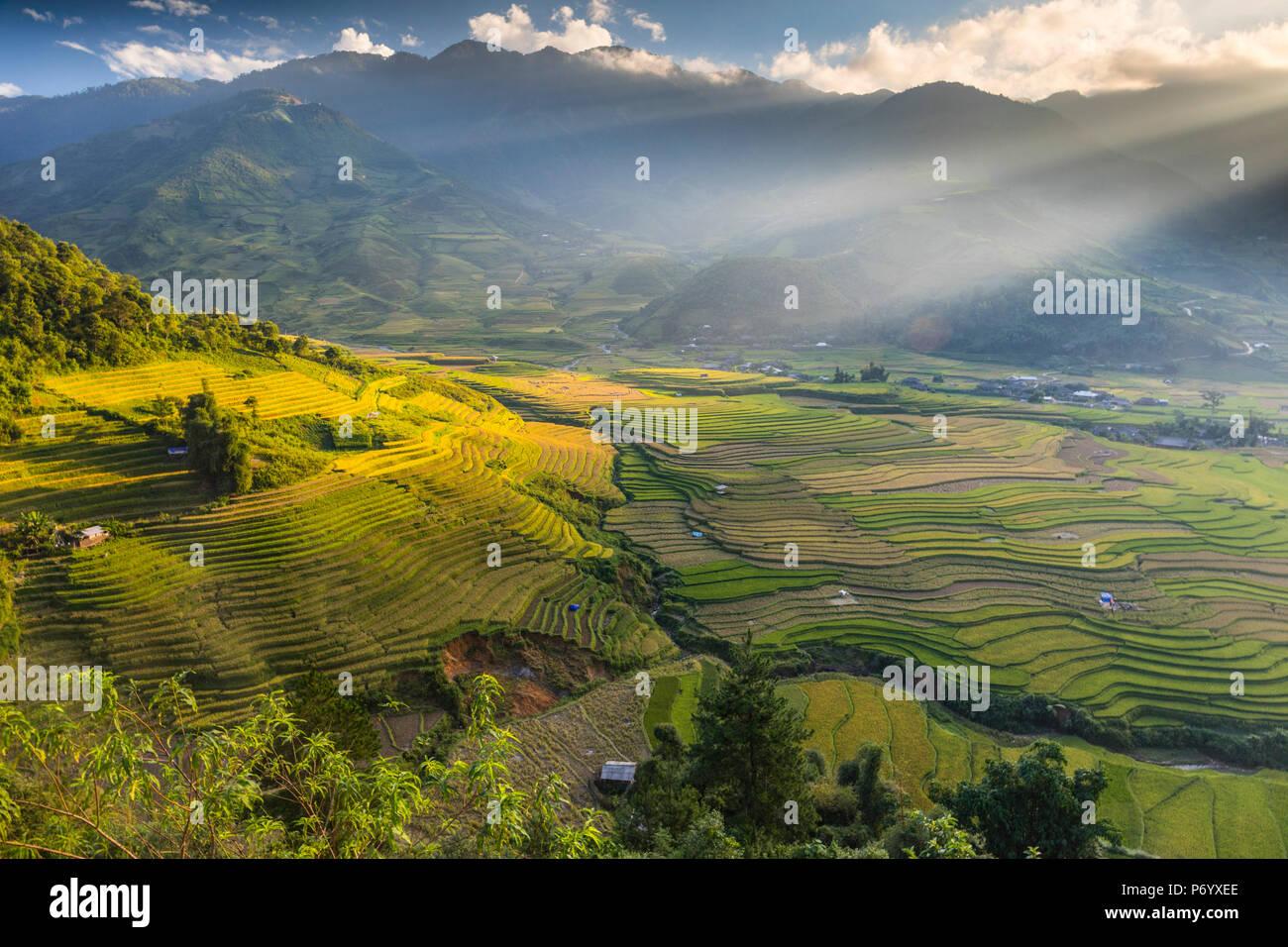 Raggi di sole sopra le montagne che circondano le terrazze di riso a Tu Le, Yen Bai Provincia, Vietnam, sud-est asiatico Foto Stock
