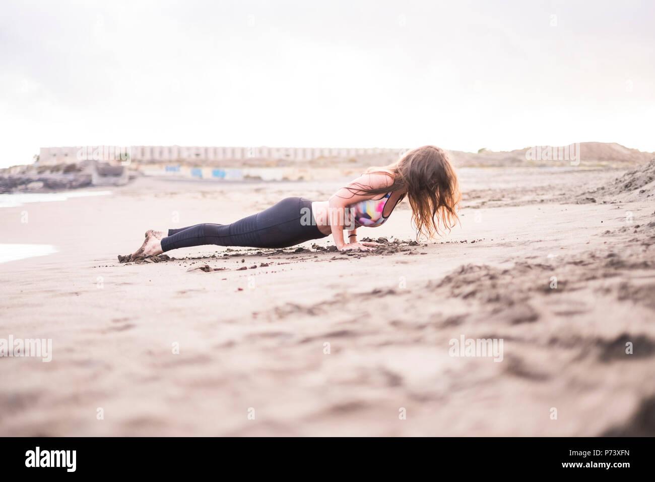 Plank perfetto per la giovane e bella signora caucasica presso la spiaggia sulla riva. giornata soleggiata nel tempo libero attività sportiva in forza e exerc bilanciato Immagini Stock