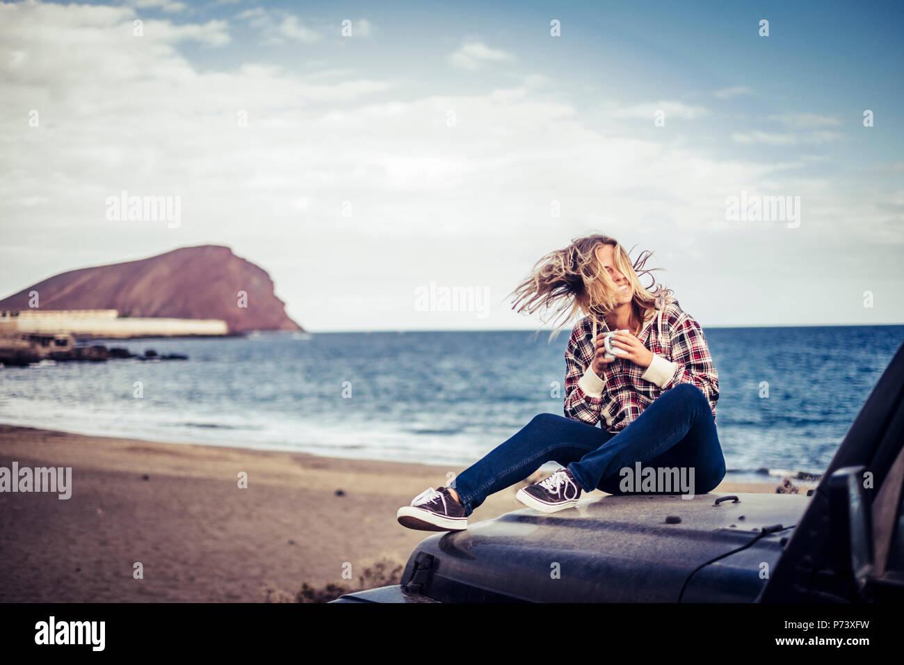 Felice bella bionda ragazza giovane soggiorno all'aperto godendo il tempo e la corsa con off road nero auto. wanderlust concetto parcheggiato sulla sabbia a t Foto Stock