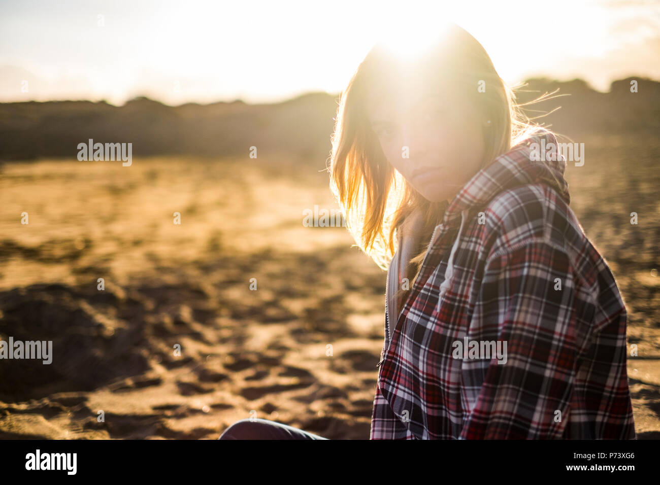 Grande bella luce dorata in un tramonto con la bionda attraente persone molde seduto alla spiaggia. vacanze e viaggi wanderlust per active girl look Immagini Stock