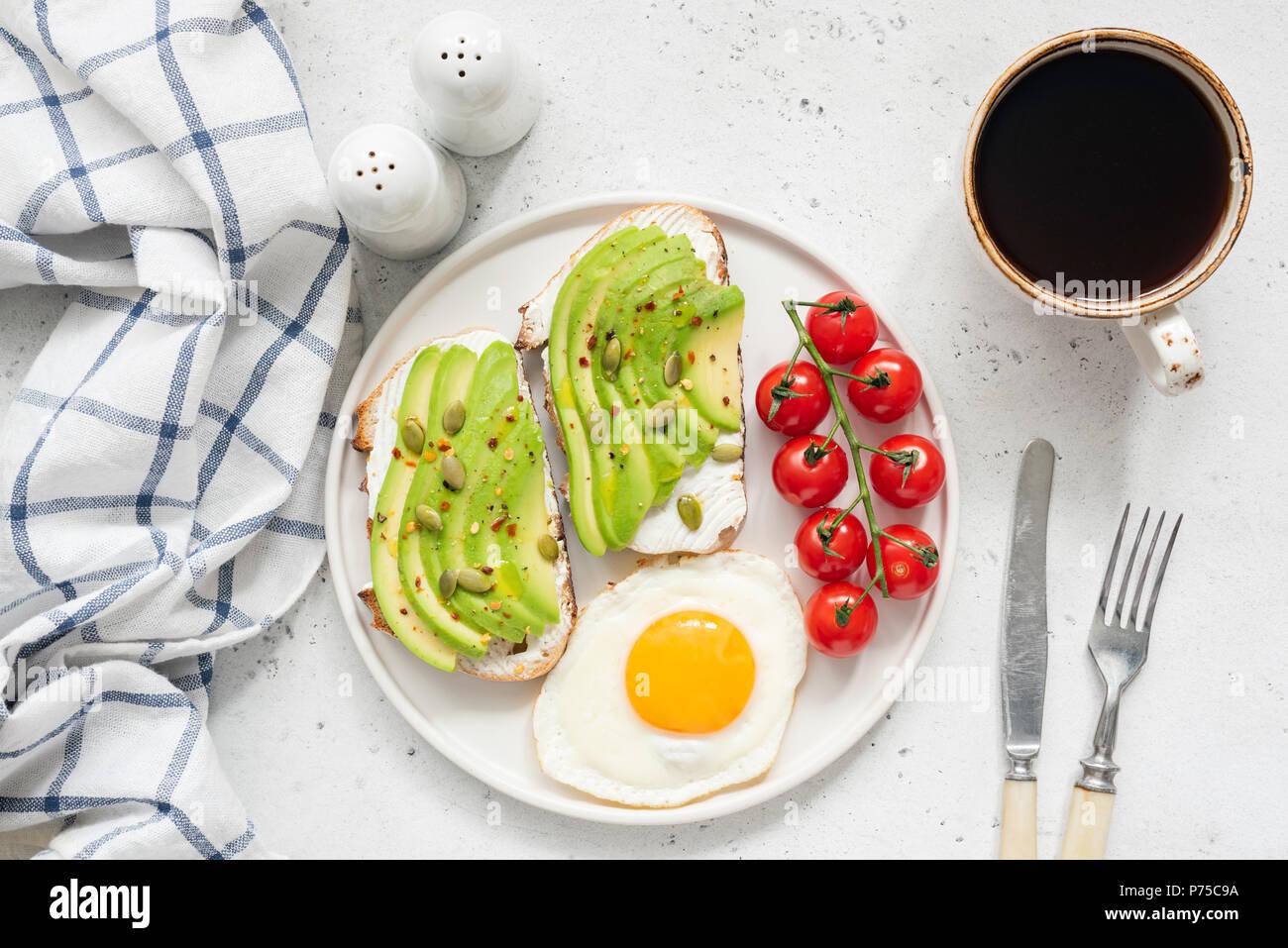 Avocado toast, uova e caffè per colazione. Vista dall'alto di una sana prima colazione. Due toast con avocado e crema di formaggio, soleggiato lato fino all'uovo, pomodoro ciliegino Immagini Stock