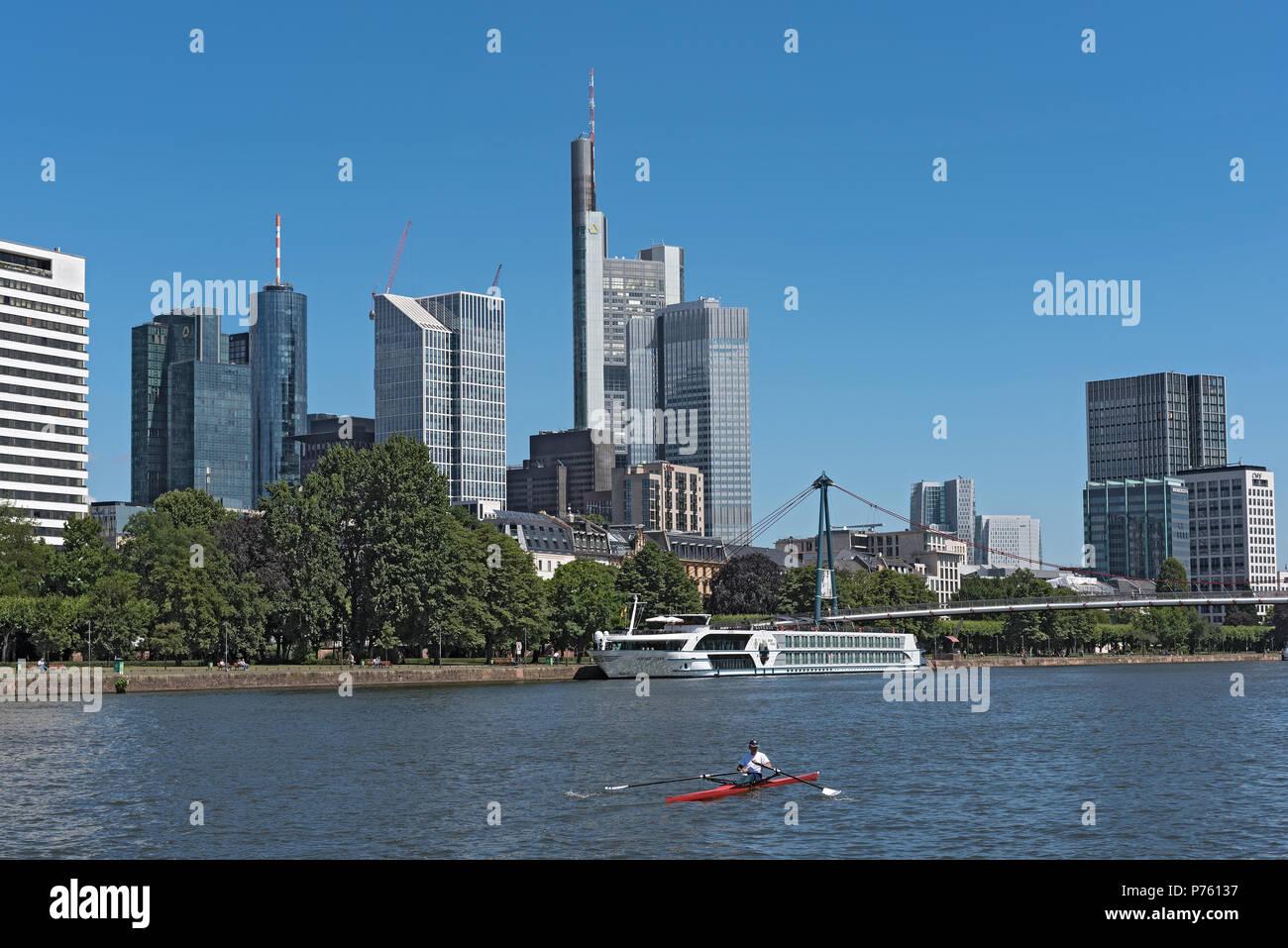 Vogatore in rosso barca sul fiume principale nella parte anteriore della skyline, Francoforte, Germania Immagini Stock