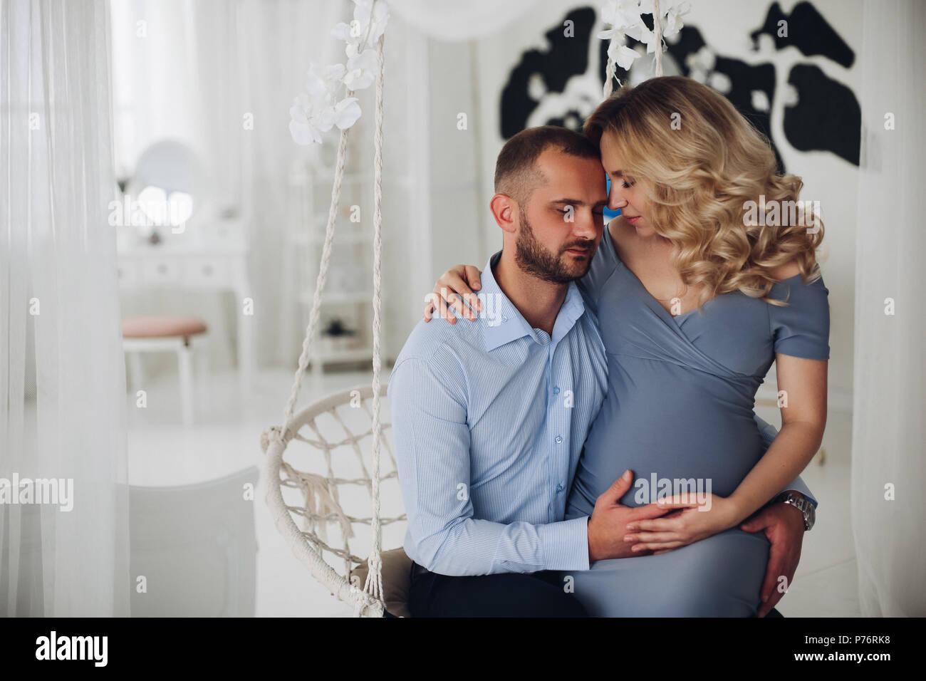 Beautiiful giovane della donna incinta e suo marito abbracciando. Immagini Stock