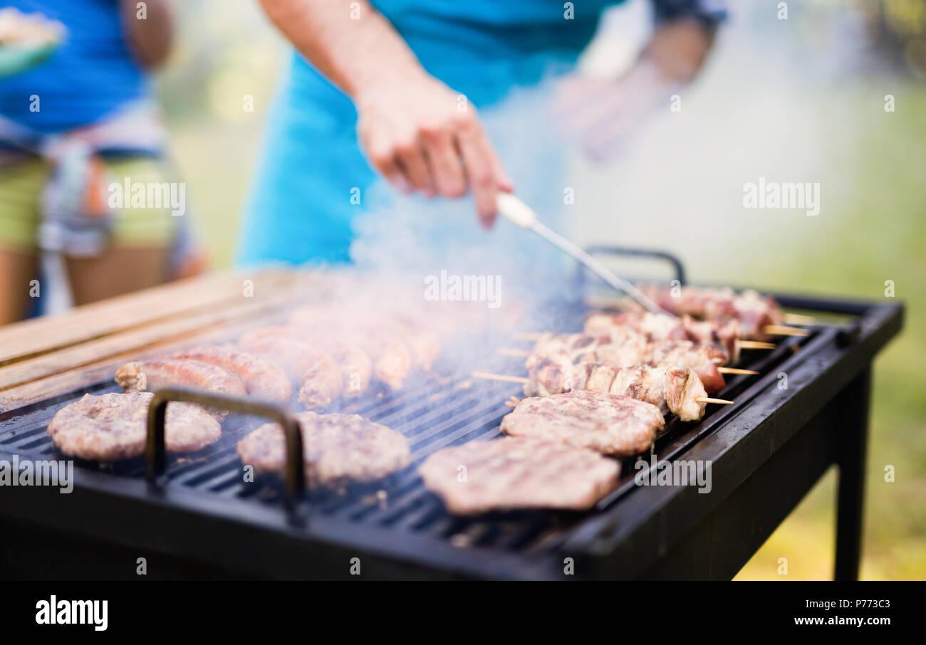 Felice gli studenti aventi un barbecue sul giorno di estate Immagini Stock