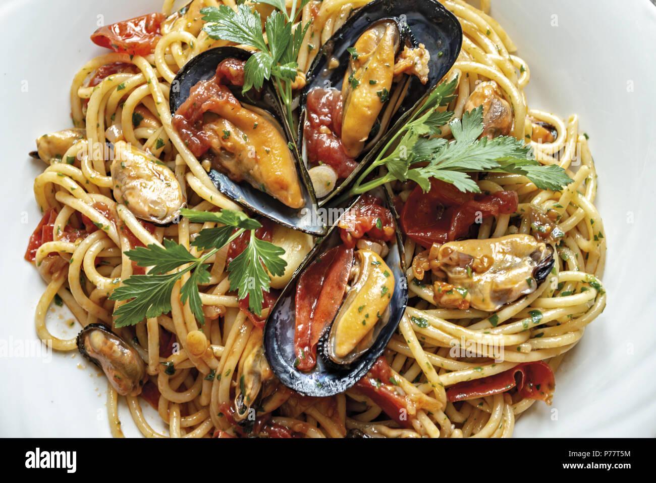Gli spaghetti con le cozze pomodoro e prezzemolo Immagini Stock