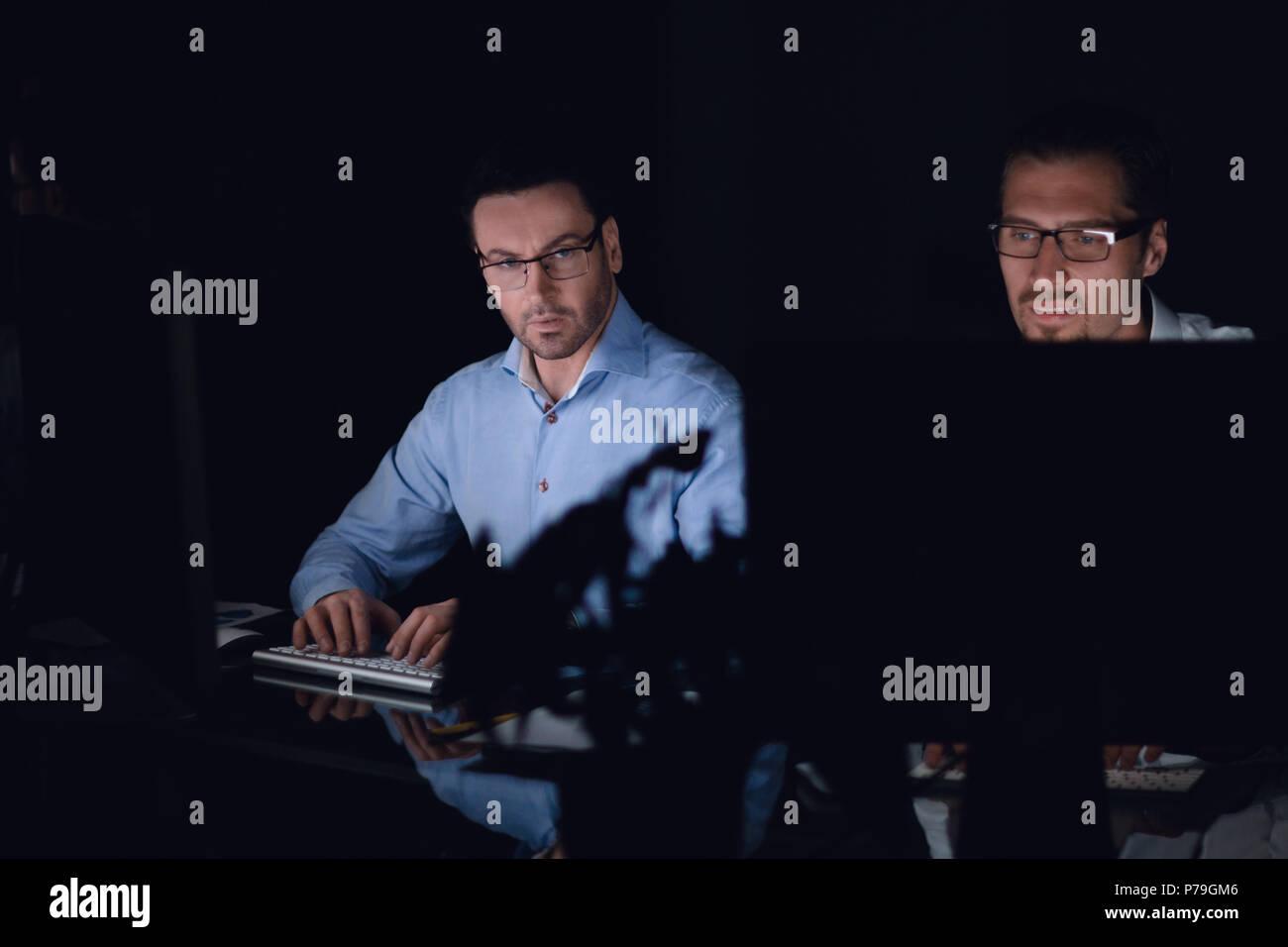 Close up.i dipendenti a lavorare sul computer in un ufficio scuro Immagini Stock