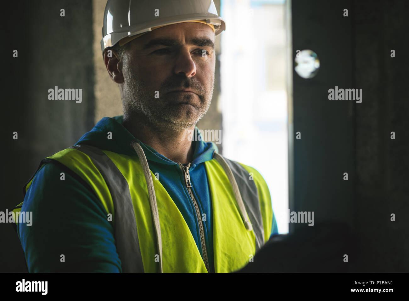 Ingegnere facendo un controllo di livello sulla parete al sito in costruzione Immagini Stock