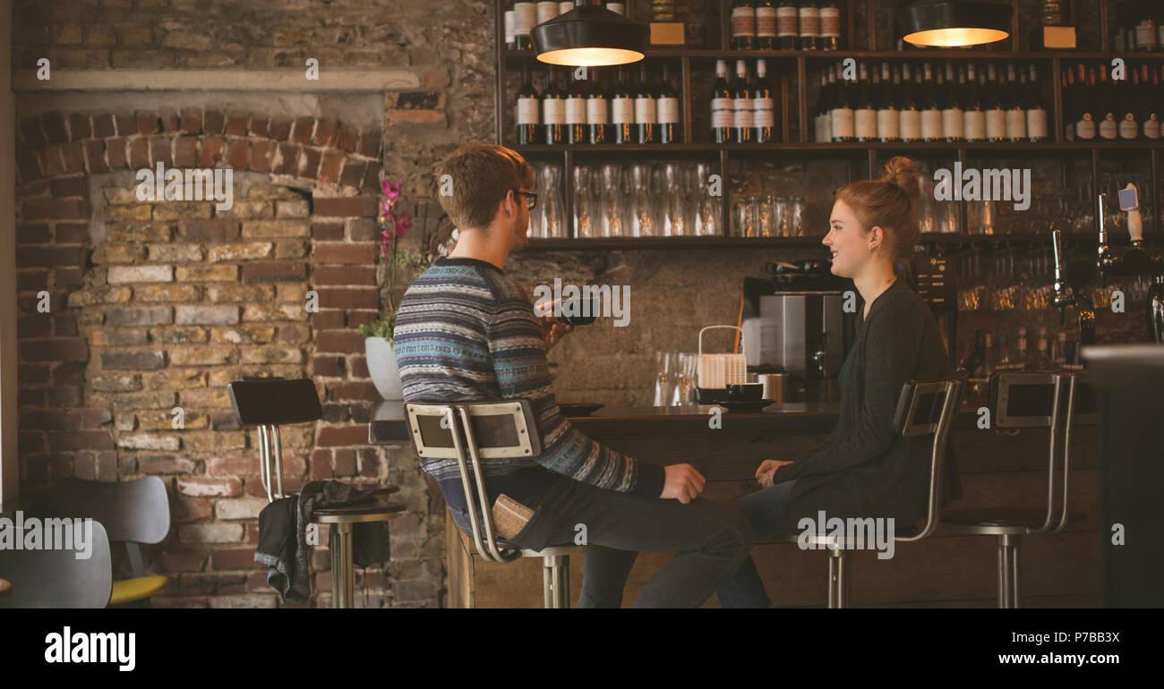 Matura un caffè mentre è seduto al banco bar Immagini Stock