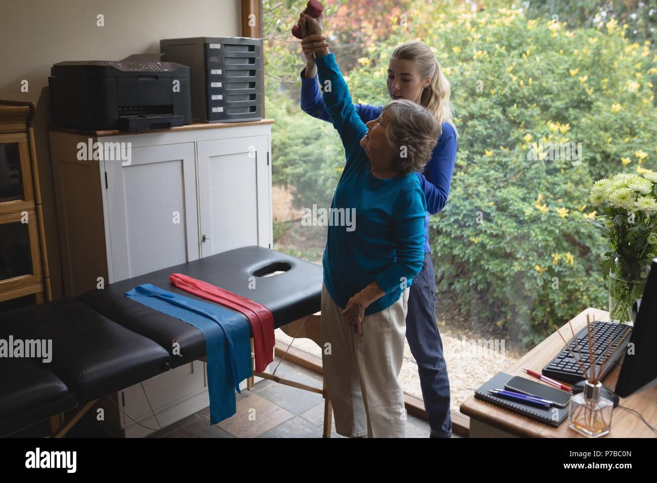 Fisioterapista assistere una donna senior con esercizi di fisioterapia Immagini Stock