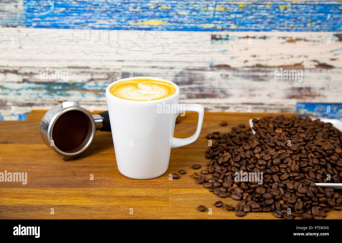 Una tazza di latte, cappuccino o caffè espresso con latte mettere su un tavolo in legno scuro con chicchi di caffè tostati Immagini Stock