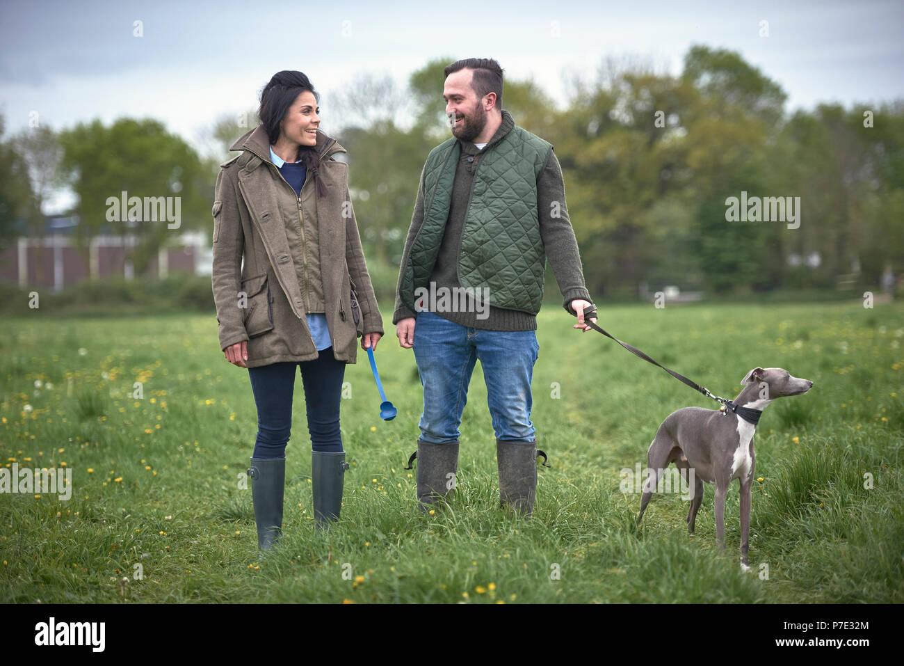 Donna e uomo a camminare cane nel campo Immagini Stock