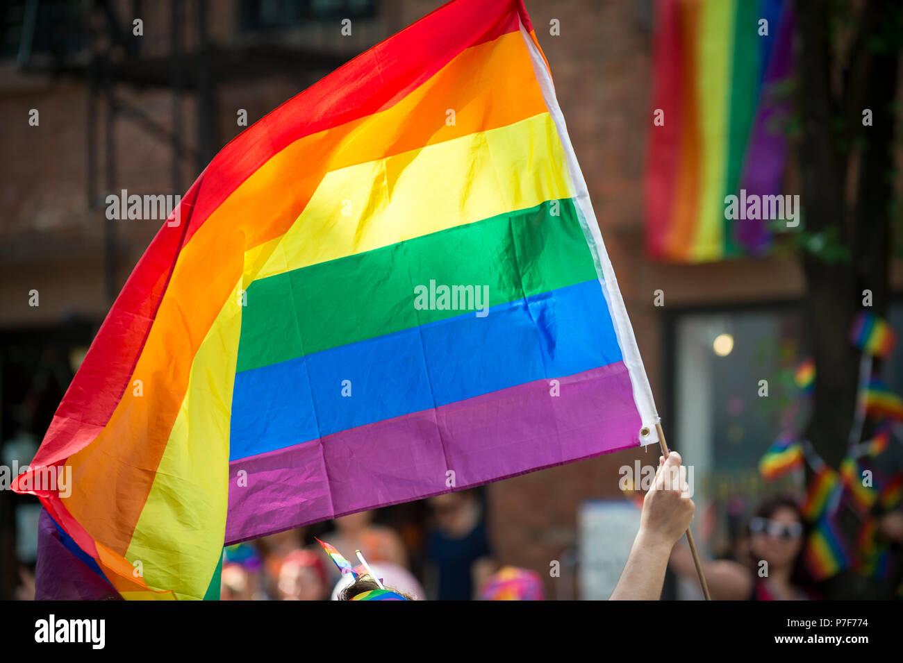 Partecipante con grande retroilluminato bandiera arcobaleno nel bilancio annuale Gay Pride Parade mentre passa attraverso il Greenwich Village. Immagini Stock