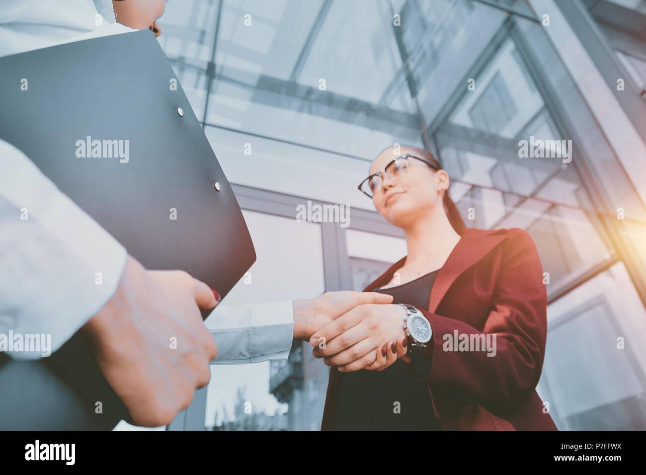 Stretta di mano di due giovani ragazze contro lo sfondo di un multi-storey edificio per uffici. Fare un affare. Relazioni amichevoli. Personale di ufficio. Immagini Stock