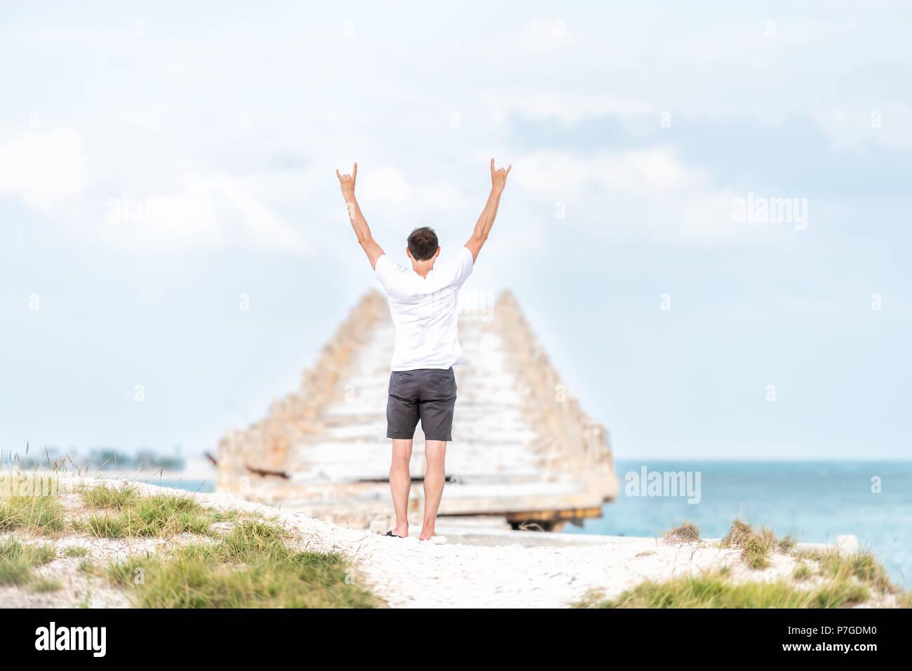 Giovane uomo in piedi di fronte a Cavalieri Key-Pigeon Key-Moser Channel-Pacet Canale (Ponte Vecchio Seven Mile Bridge) con entrambe le braccia sollevate in aria Immagini Stock