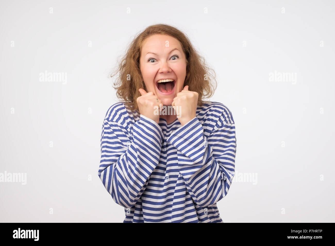 Sorpreso giovane donna sorridente e tenendo le sue palme vicino al viso. Ella è sconvolto con i prezzi di vendita. è vero. Immagini Stock