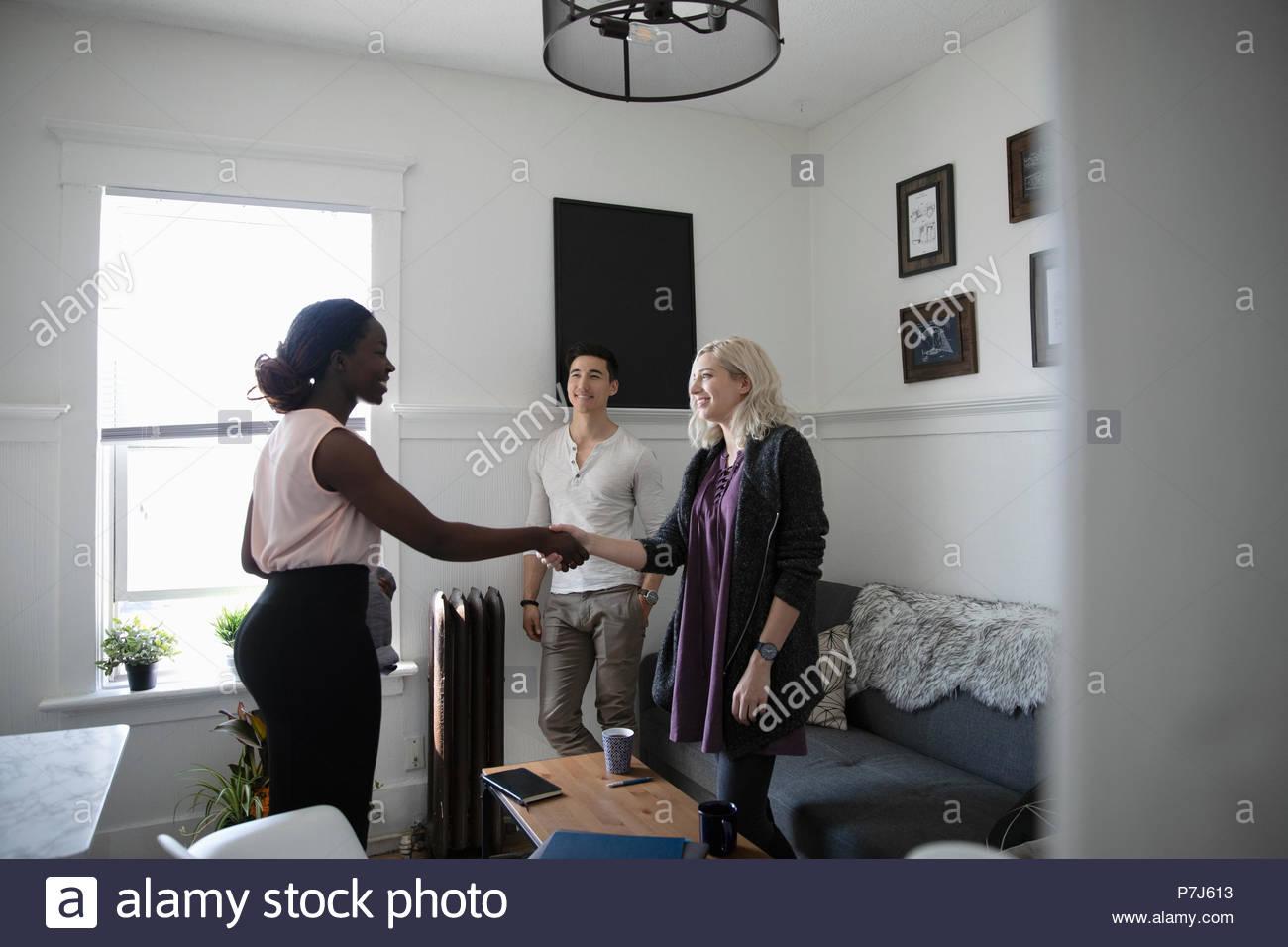 Advisor finanziario consulenza con coppia giovane in salotto Immagini Stock