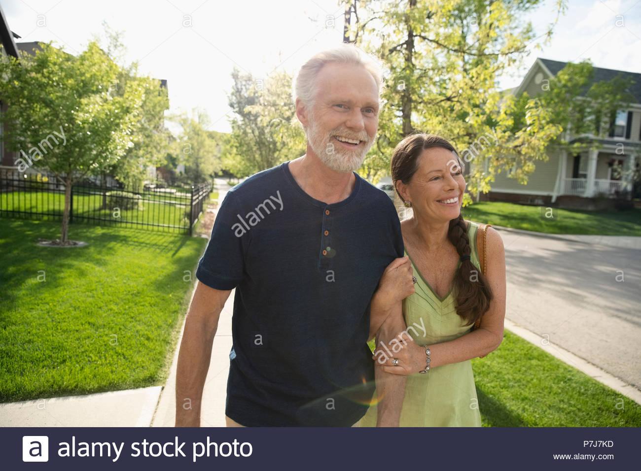 Sorridente, affettuosa coppia senior camminare a braccetto sul quartiere soleggiato marciapiede Immagini Stock