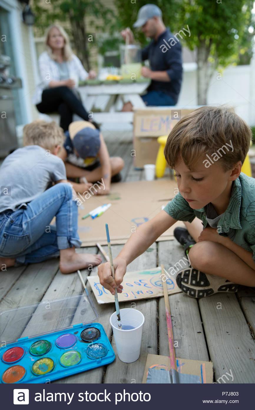 Famiglia rendendo la limonata e pittura di cartone stand limonata in back yard Immagini Stock