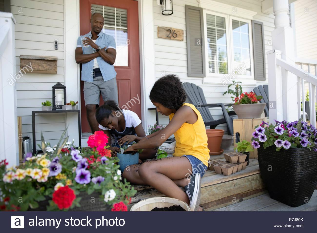 Padre guardando tween figlie potting fiori sulla parte anteriore stoop Immagini Stock