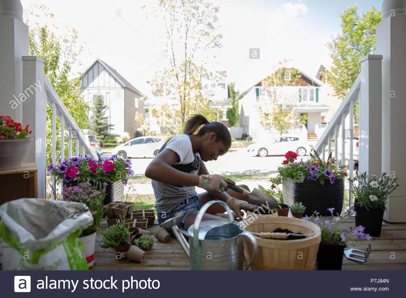 Tween girl potting piante e fiori sulla parte anteriore stoop Immagini Stock