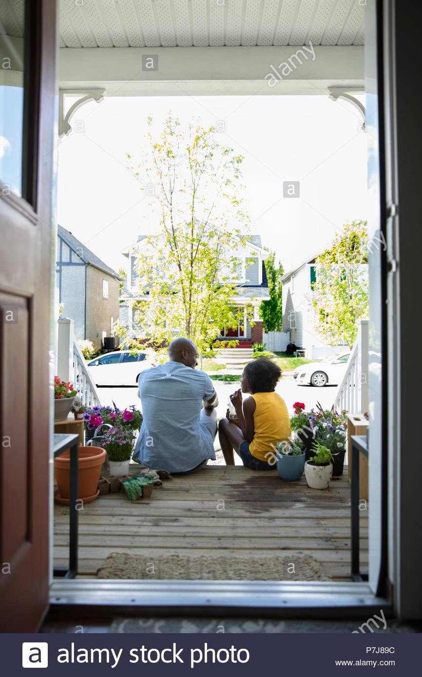 Padre e figlia di incollaggio, piantare fiori sulla parte anteriore stoop Immagini Stock