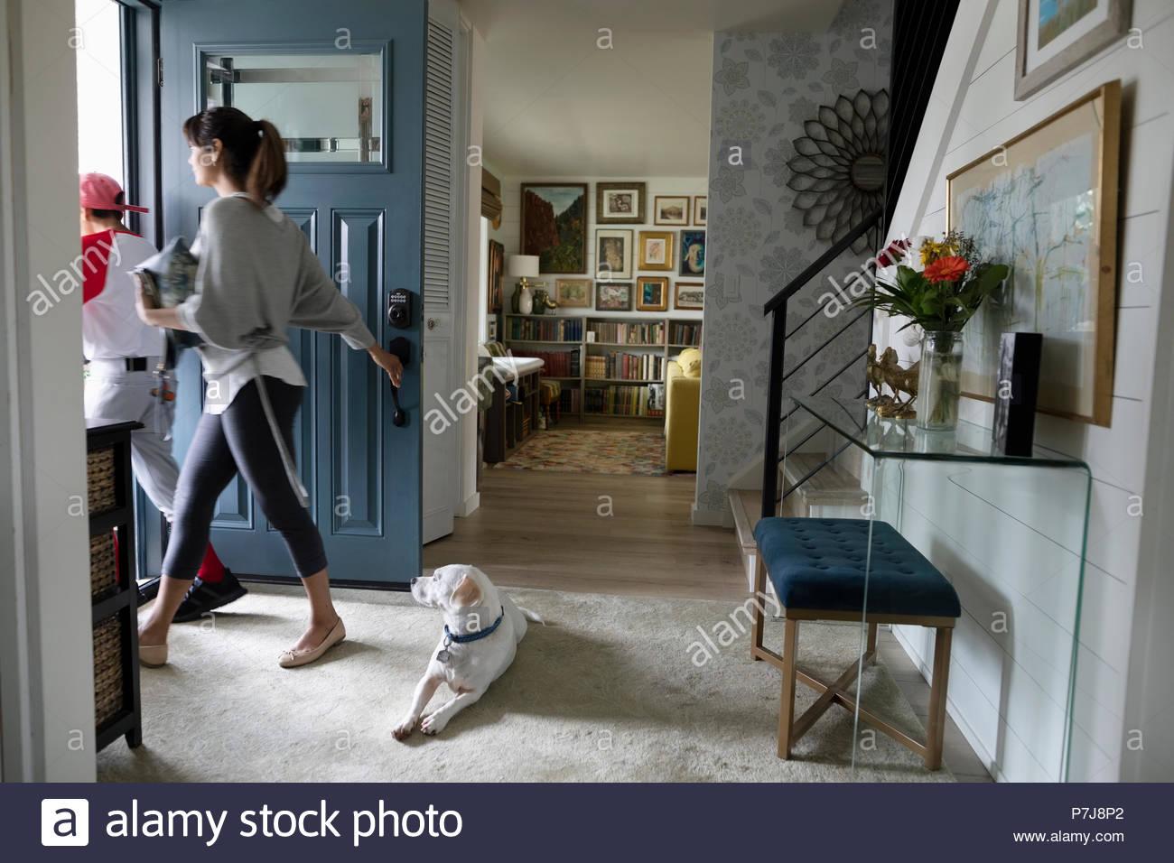Cane guarda la madre e il figlio di lasciare per la pratica di baseball a sportello anteriore Immagini Stock