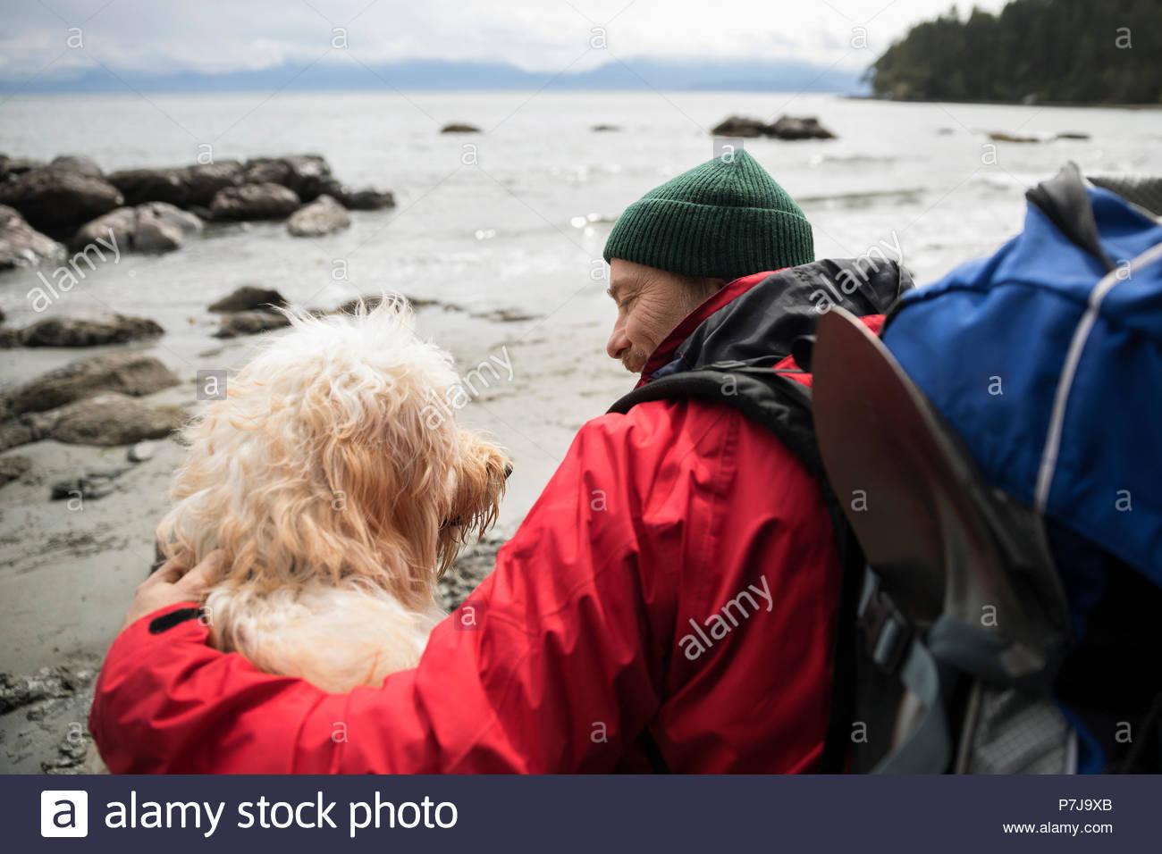 Uomo e cane backpacking sulla spiaggia robusto Immagini Stock