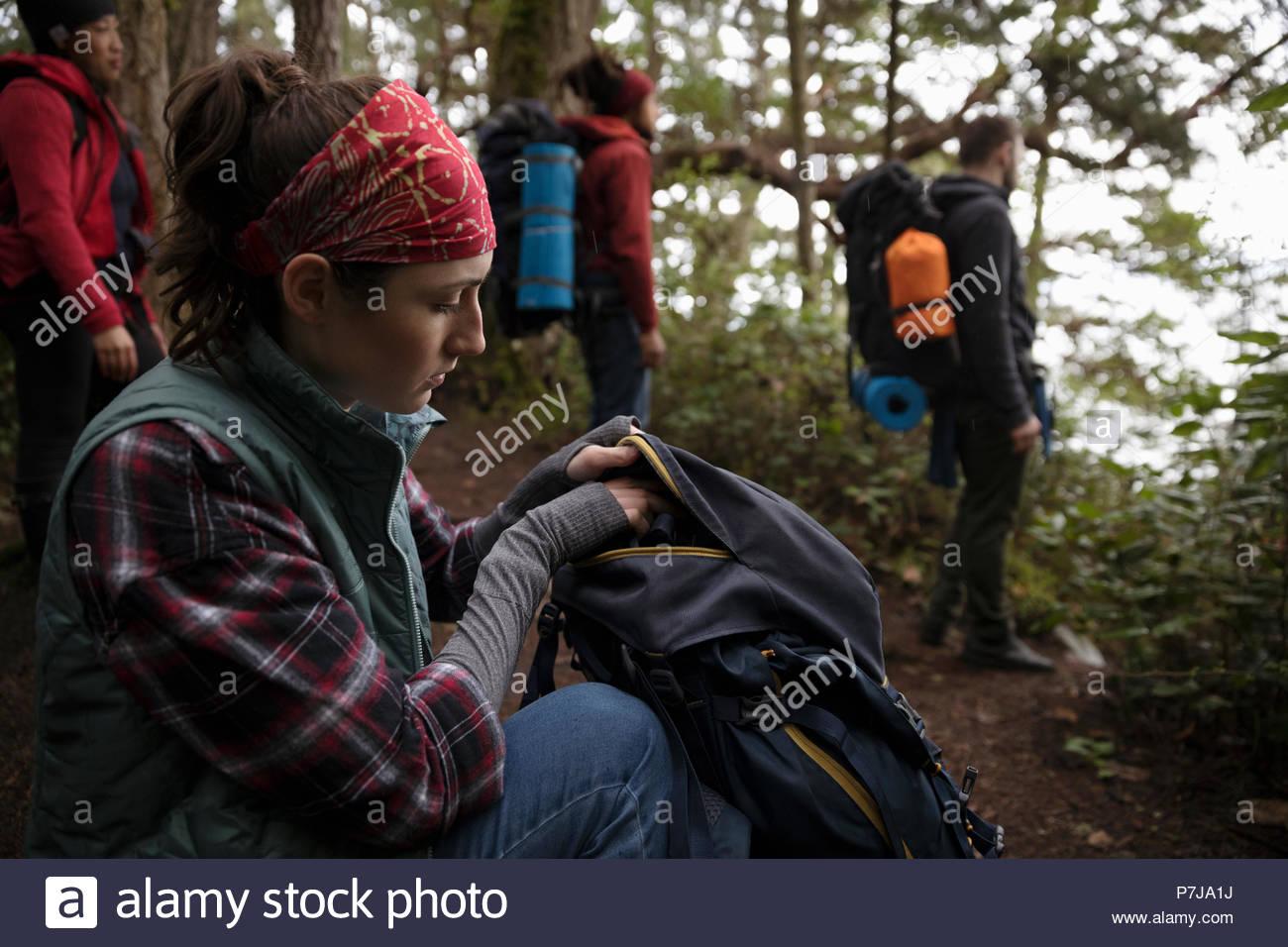 Woman Backpacking nei boschi con gli amici, cercando nello zaino Immagini Stock