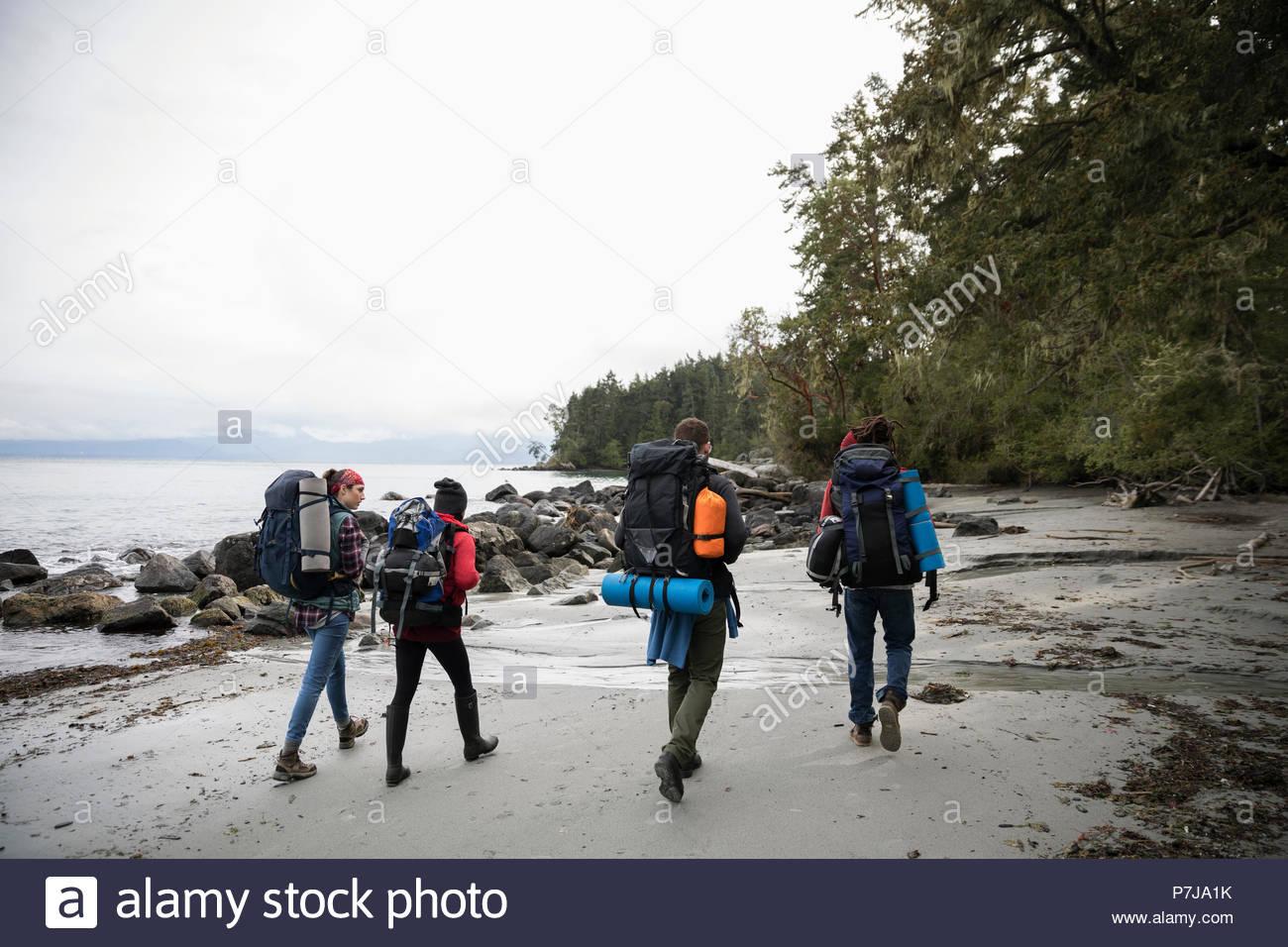 Amici backpacking sulla spiaggia robusto Immagini Stock