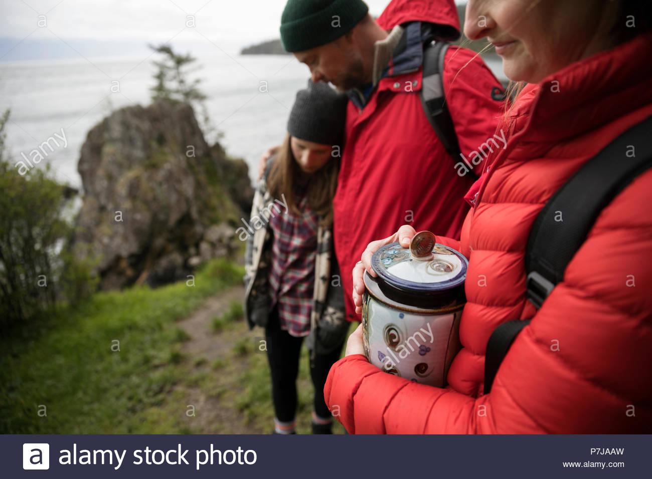 Famiglia con urna diffusione di ceneri sulla scogliera con vista sull'oceano Immagini Stock