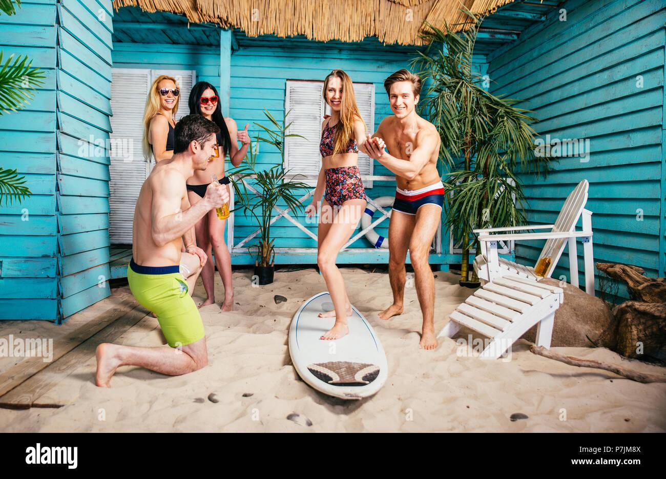 Il gruppo di cinque amici celebrando nella loro estate beach house Foto Stock