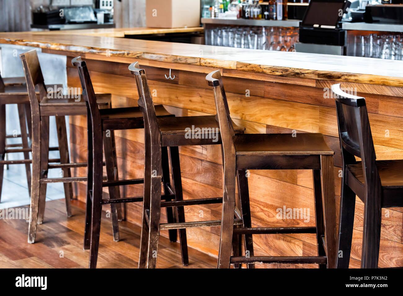 Fila di vuoto vintage in legno sgabelli bar dal contatore nel bere