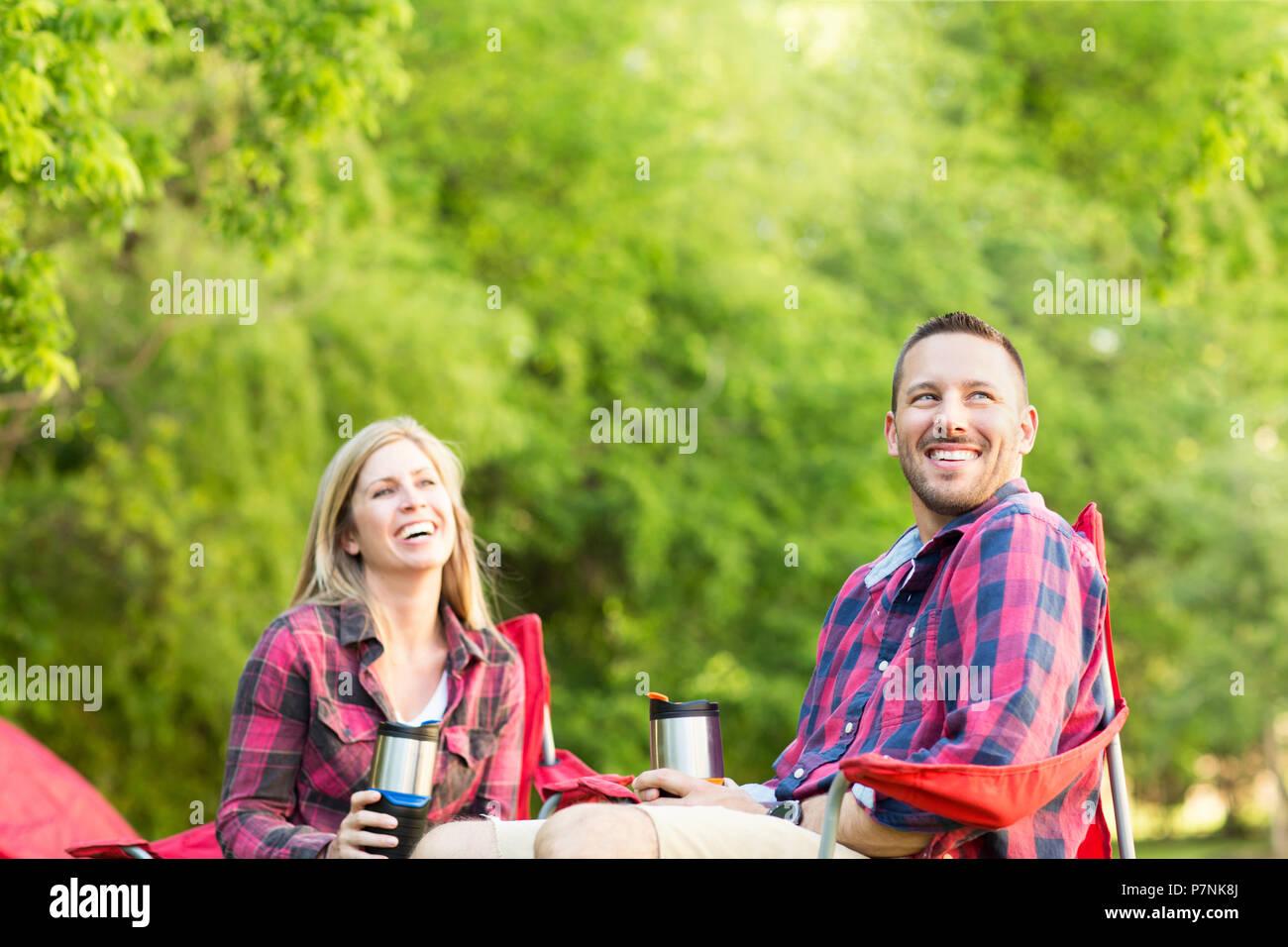 Paio di parlare e ridere su un viaggio di campeggio. Immagini Stock