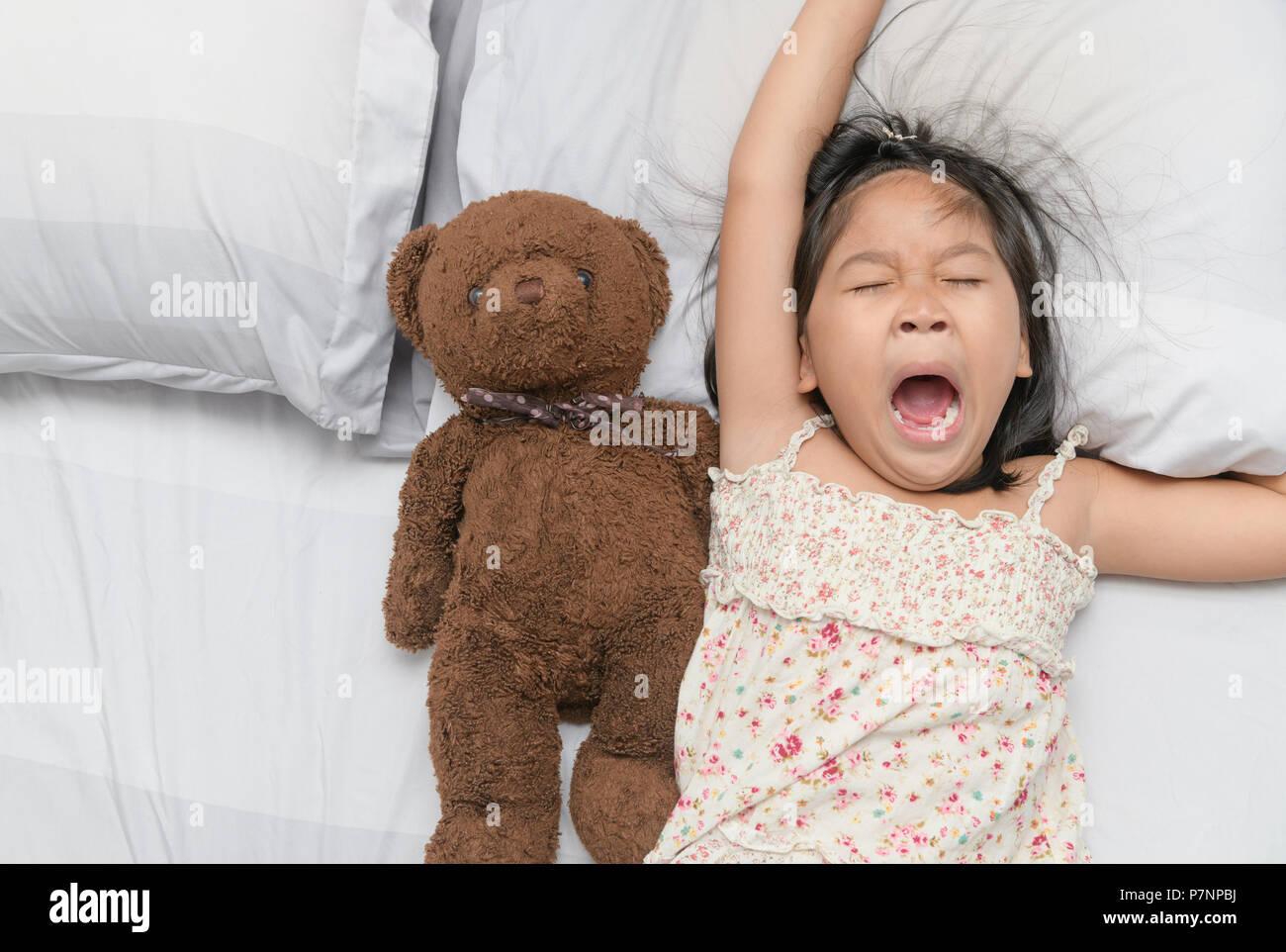 Bambina sbadiglio e dormire sul letto con Teddy bear bambola, assistenza sanitaria e concetto di rilassamento Immagini Stock