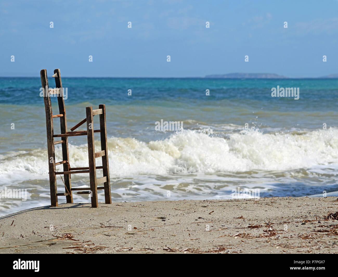 Vecchio rotto sgabello in legno sulla spiaggia e il mare in