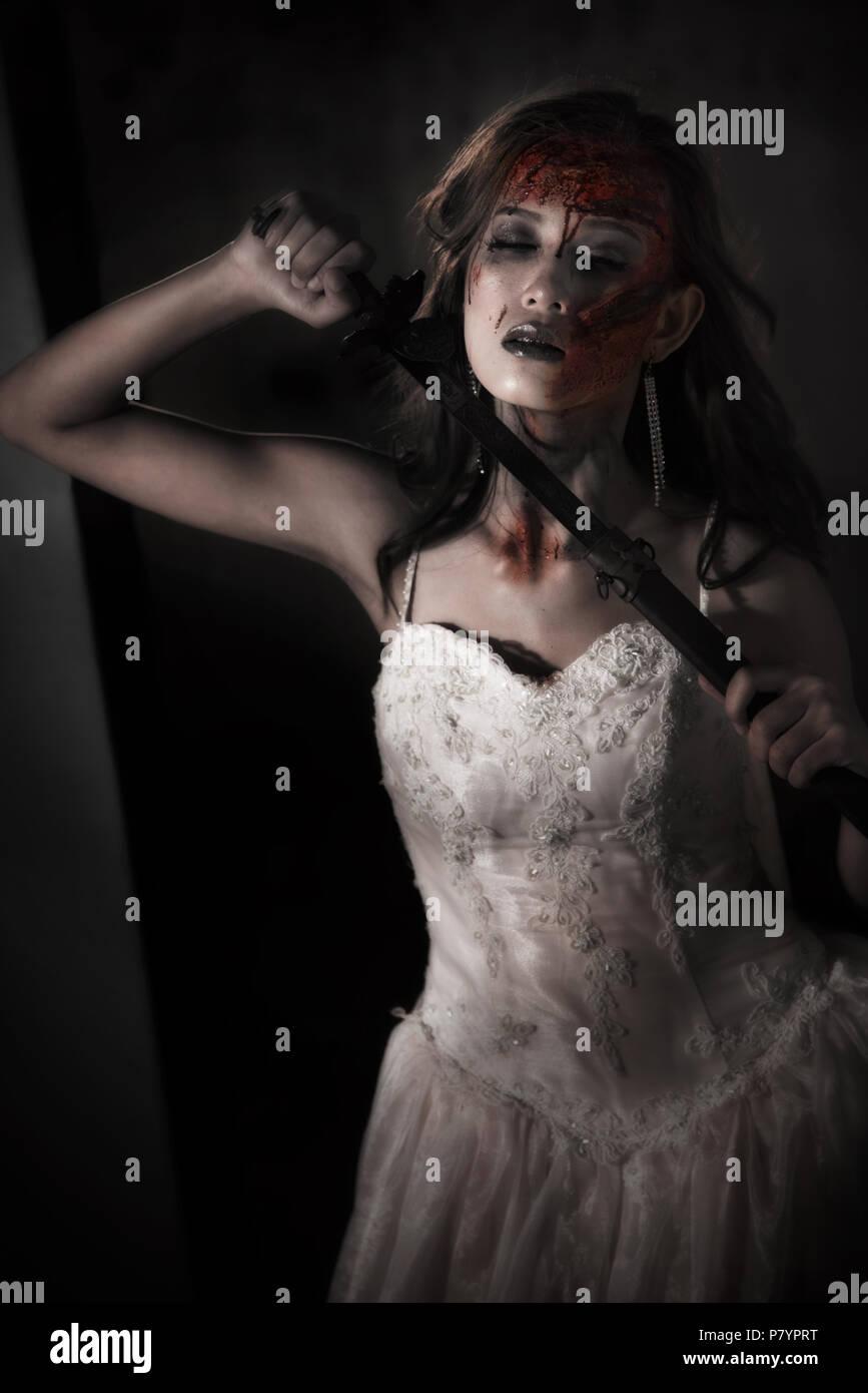 Signora Zombie corpse la spada per uccidersi durante il matrimonio. Orrore e concetto di fantasma per Halloween il giorno dell evento a tema. Dark e grunge film di tono Immagini Stock