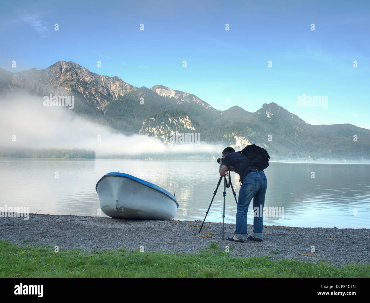 L'uomo escursionista è tenuto foto della nave al mountain lake shore. Silhouette a la pesca in barca a remi sul lago di costa. Immagini Stock
