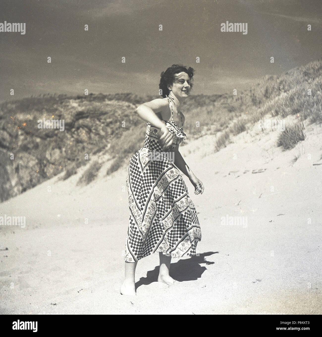 Degli anni Cinquanta, estate e una giovane donna in un lungo abito modellato la riproduzione di frisbee su di una spiaggia di sabbia, Inghilterra, Regno Unito. Foto Stock
